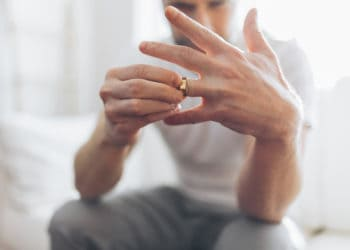 Heartbroken man holding a wedding ring